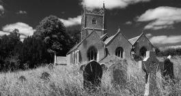 Monochrome image of Landulph Church looking across the graveyard, with dramatic skies
